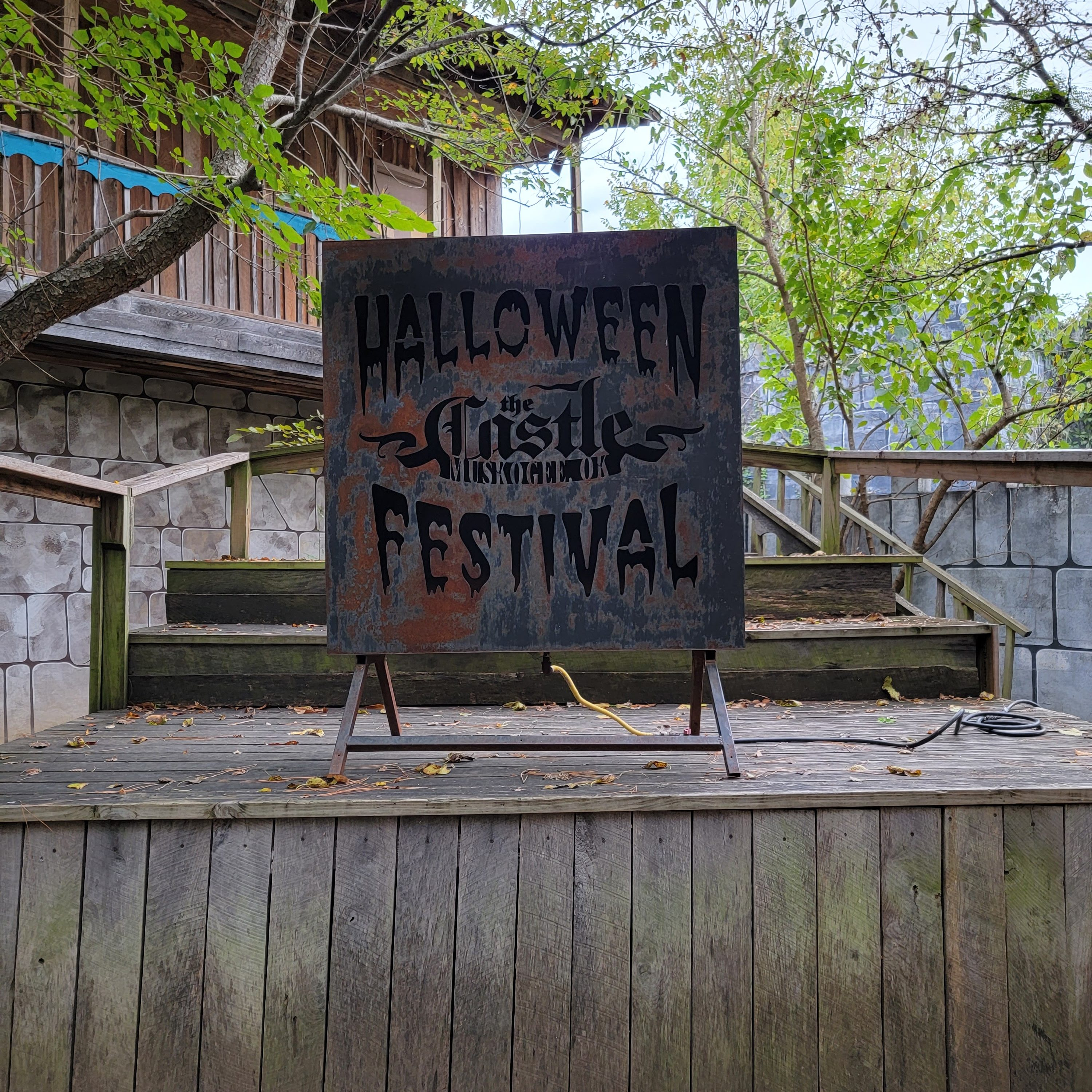 """Image shows a metal sign atop a wooden platform. The sign reads """"Halloween Festival at The Castle Muskogee"""""""